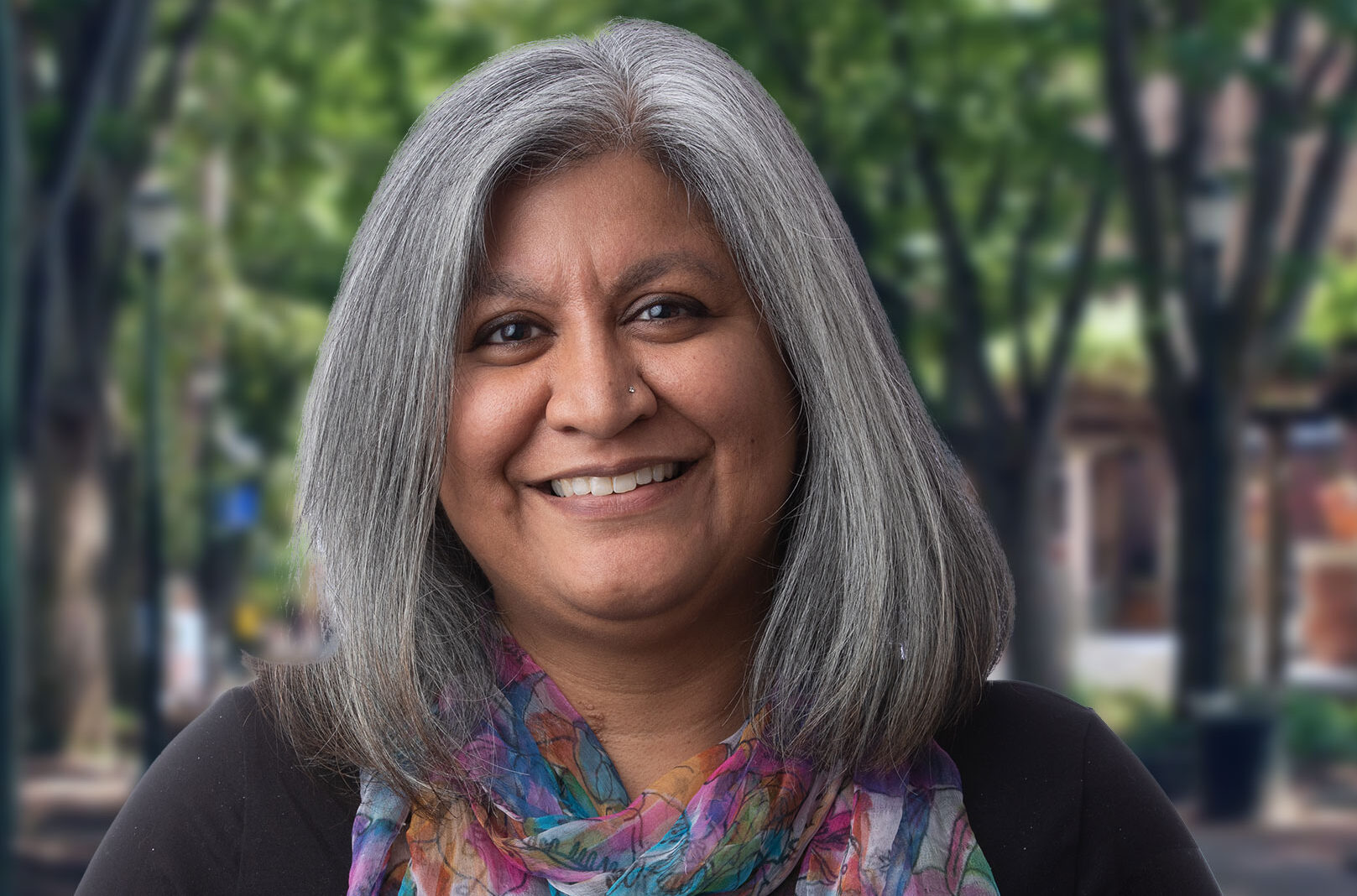 Mamta Accapadi standing in front of trees and buildings on Penn's campus