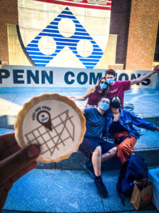 You are here cookie with students in the back posing by the Penn Sheild on Penn Commons