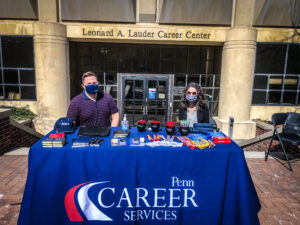 Staff giving away swag at from Career Services for the Porch Parties