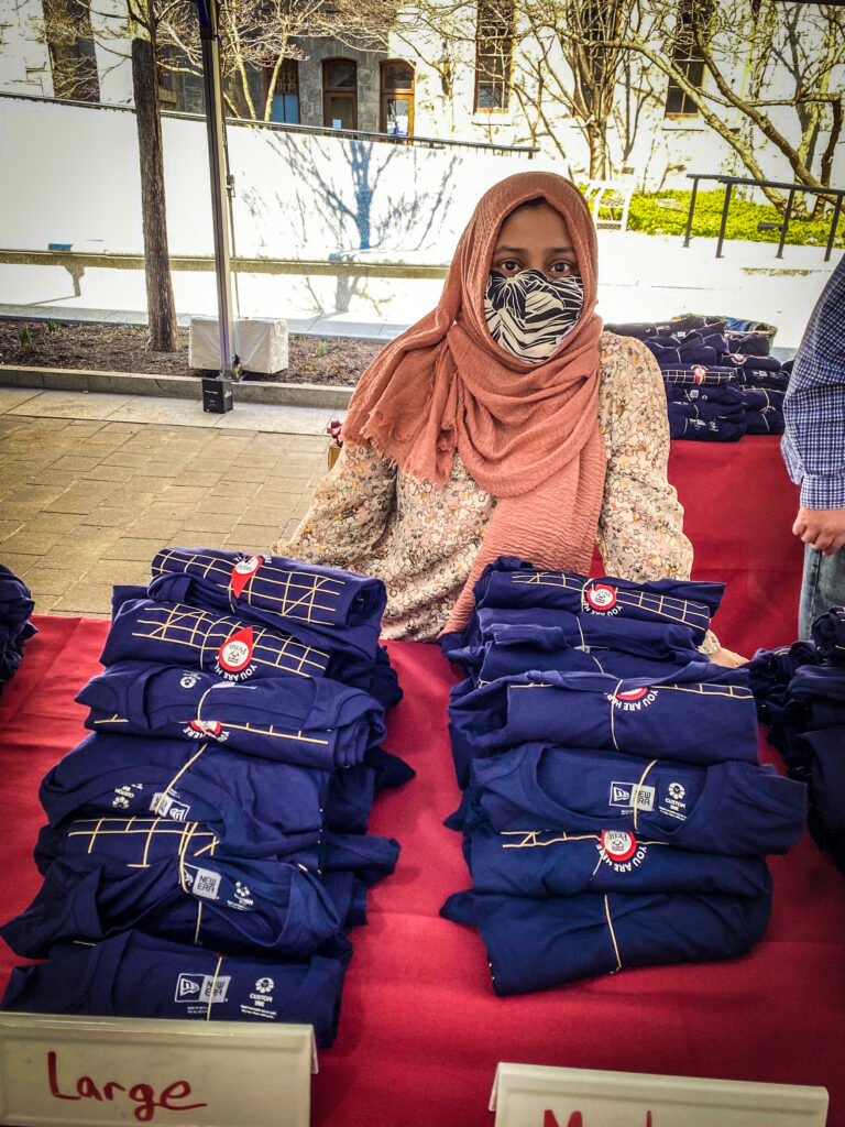 Staff member giving away tshirts for University Life Grab and Greet