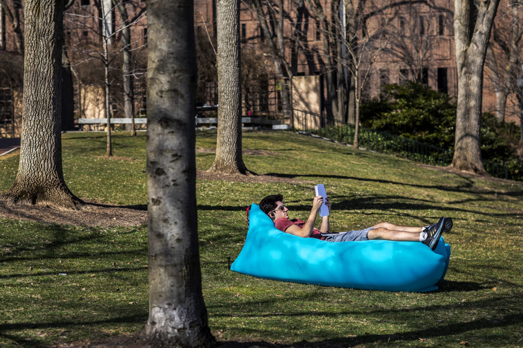 Student reading on College Green during Spring Stay