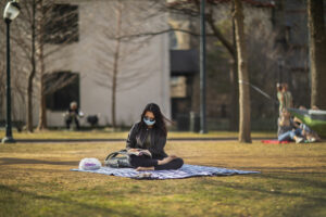 Student reading on the grass during Spring Stay