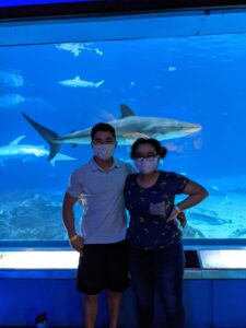 Two students posing in front of a shark at the Aquarium for Spring Stay 2021