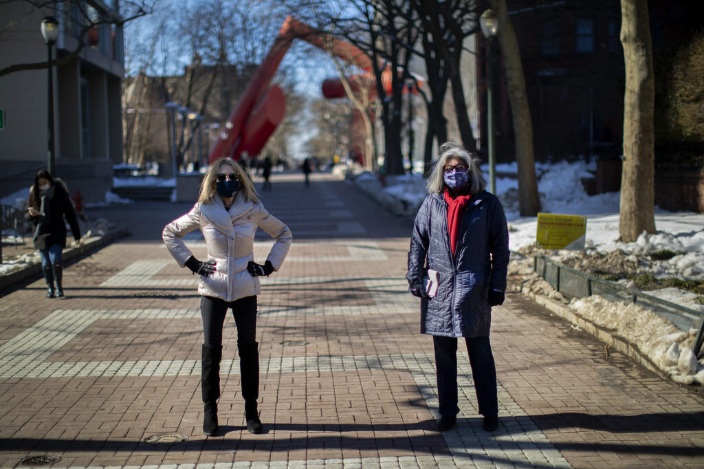 Amy Gutmann with Mamta Accapadi masked on Locust Walk in front of the Covenant art sculpture